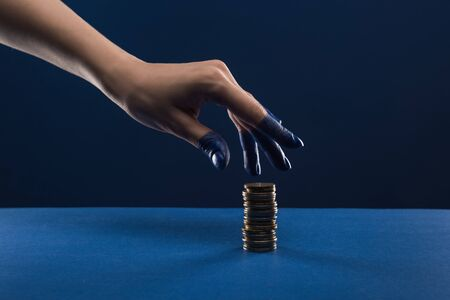 cropped view of female hand with painted fingers touching coins isolated on blue Stockfoto