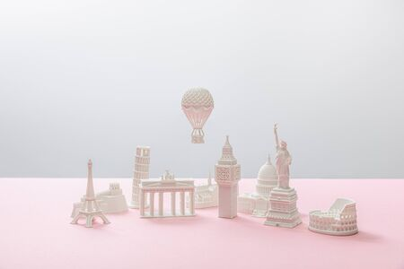 small figurines from different countries on grey and pink 免版税图像