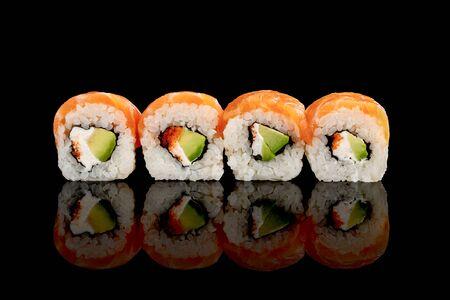 fresh delicious Philadelphia sushi with avocado, creamy cheese, salmon and masago caviar isolated on black