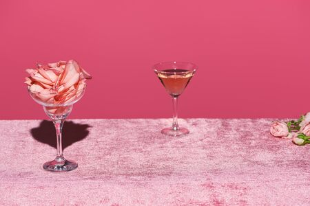 rose petals in glass near rose wine on velour pink cloth isolated on pink, girlish concept Stock Photo