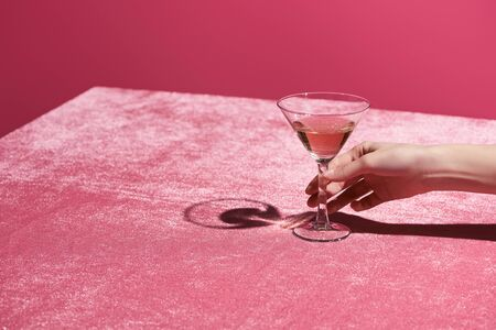 cropped view of woman holding glass with drink on velour cloth isolated on pink, girlish concept