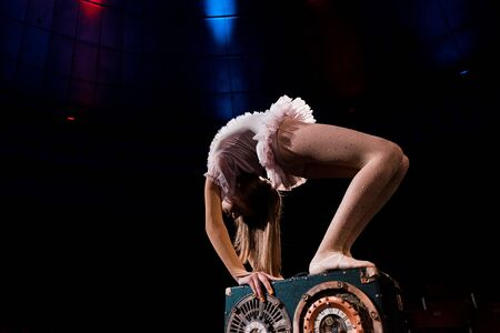 flexible young woman in costume performing in circus
