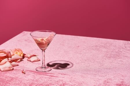 rose petals near glass on velour pink cloth isolated on pink, girlish concept
