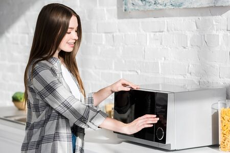 smiling and attractive woman in shirt using microwave in kitchen