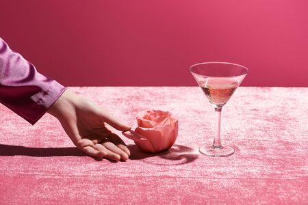 female hand near rose and glass of rose wine on velour cloth isolated on pink, girlish concept Stok Fotoğraf