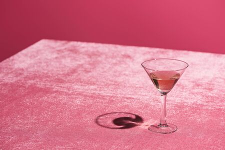 alcohol drink in glass on velour pink cloth isolated on pink, girlish concept Stock Photo