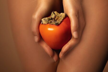 cropped view of woman in nylon tights holding ripe persimmon isolated on brown