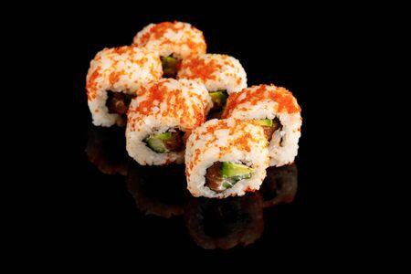 délicieux California roll avec avocat, saumon et caviar de masago isolé sur fond noir Banque d'images