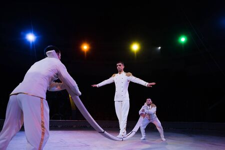 selective focus of handsome air acrobat balancing on pole near men in circus 版權商用圖片