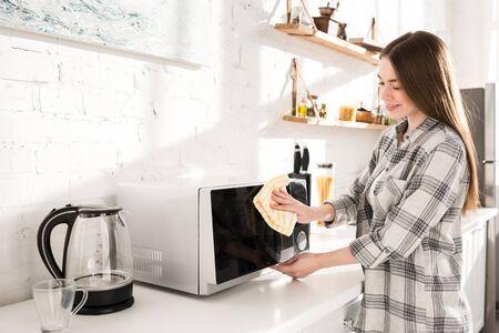 lächelnde und attraktive Frau, die Mikrowelle mit Lappen in der Küche säubert Standard-Bild