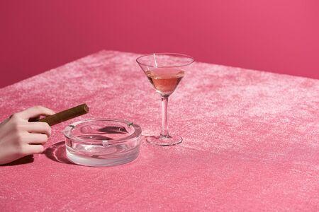 cropped view of woman holding cigar near ashtray and glass of rose wine on velour cloth isolated on pink, girlish concept