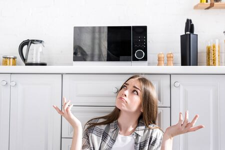 confused and attractive woman looking at microwave and doing shrug gesture in kitchen 免版税图像