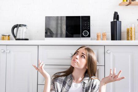 Verwirrte und attraktive Frau, die in die Mikrowelle schaut und in der Küche eine Achselzucken-Geste macht Standard-Bild