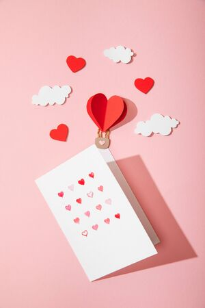 top view of greeting card with hearts in white envelope near paper heart shaped air balloon in clouds on pink