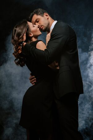 handsome man in suit hugging sensual woman on black with smoke Archivio Fotografico
