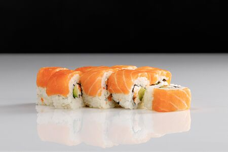 delicious Philadelphia sushi with avocado, creamy cheese, salmon and masago caviar on white surface isolated on black