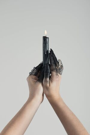 Cropped view of witch with black paint on hands holding burning candle isolated on grey Imagens