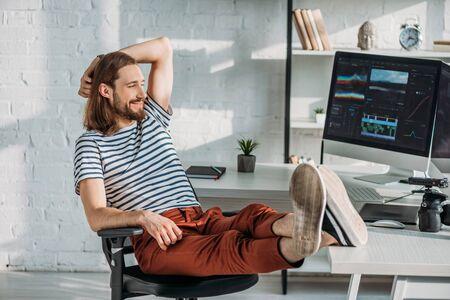 happy filmmaker resting near computer monitors in studio