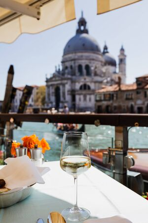 selective focus of wine glass on table and Santa Maria della Salute church on background Stock Photo