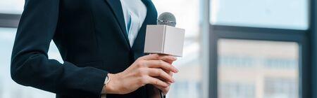 panoramic shot of journalist holding microphone