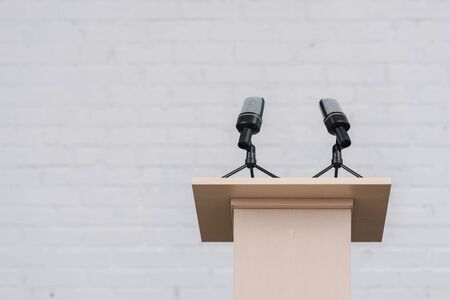 wooden stand with microphones near white brick wall