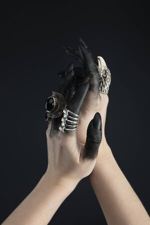Cropped view of hands of witch with jewelry rings and black dye isolated on black 免版税图像