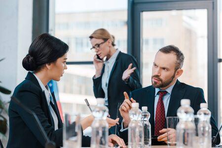 selective focus of diplomats talking and gesturing near businesswoman using smartphone Standard-Bild
