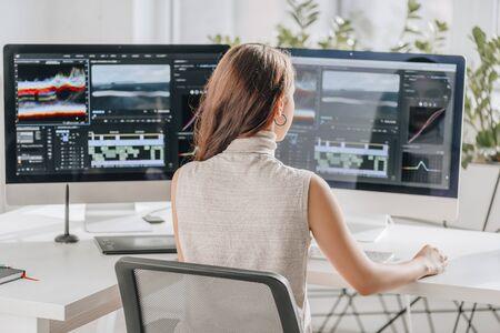 achteraanzicht van filmmaker die in de buurt van computerschermen werkt