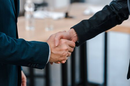 cropped view of businesswoman shaking hands with businessman Stock Photo