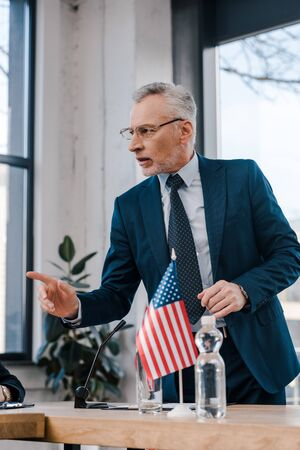 selective focus of bearded diplomat in eyeglasses pointing with finger while talking near american flag Standard-Bild