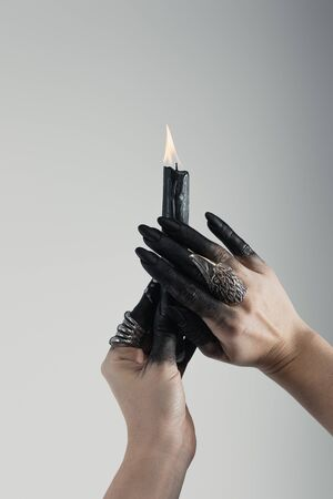 Cropped view of witch hands with black painted fingers and jewelry rings holding candle isolated on grey