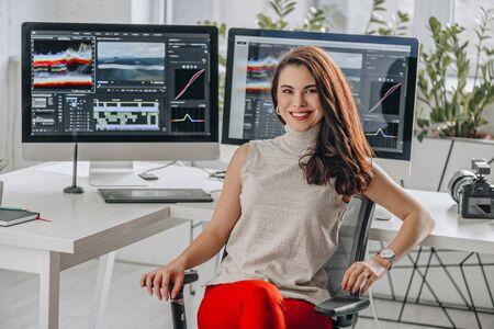 cheerful and attractive art editor near computer monitors
