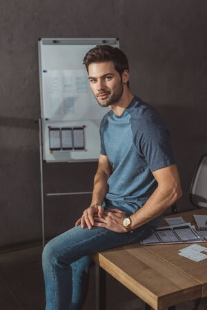 Handsome designer looking at camera while sitting on table with layouts