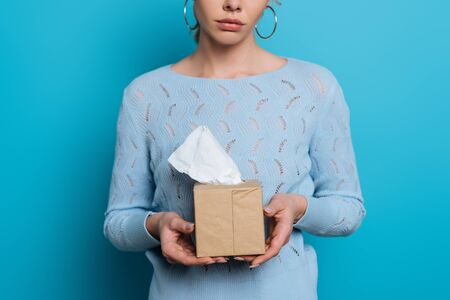 cropped view of upset girl holding pack of paper napkins on blue background