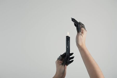 Cropped view of witch with black painted hands and jewelry rings holding candle isolated on grey with copy space Imagens