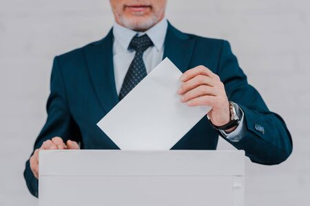 cropped view of bearded businessman voting near brick wall Stock Photo