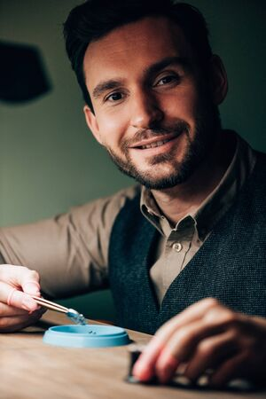 Handsome watchmaker smiling at camera while working with watch parts at table