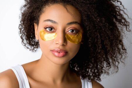 Hermosa chica afroamericana rizada con parches dorados en los ojos, aislado en gris Foto de archivo