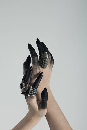 Cropped view of witch hands with black dye and jewelry rings isolated on grey 免版税图像