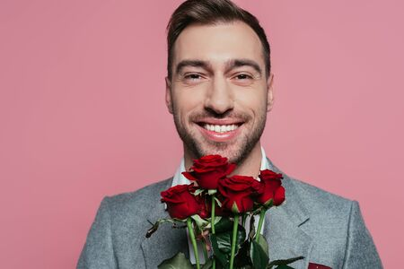 smiling man in suit holding red roses, isolated on pink Stock Photo