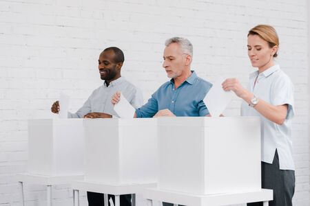 cheerful multicultural citizens voting while standing near boxes