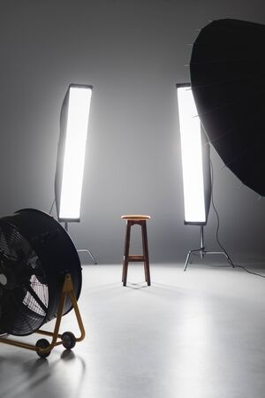fan, reflector, wooden stool and lights on backstage in photo studio