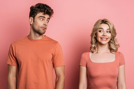thoughtful man looking at cheerful girlfriend on pink background