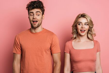 positive, tricky man and woman looking at each other on pink background