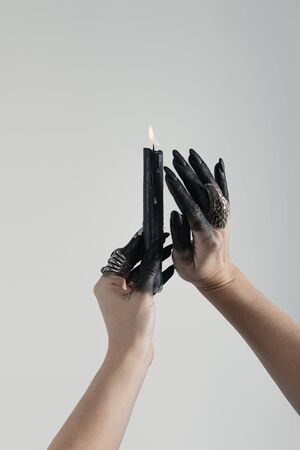 Cropped view of black painted hands of witch with jewelry rings and candle isolated on grey