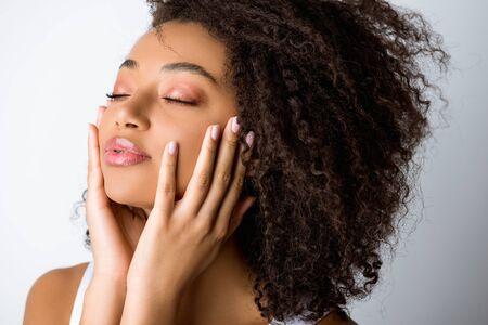 Porträt eines zarten afroamerikanischen Mädchens mit geschlossenen Augen, isoliert auf Grau Standard-Bild