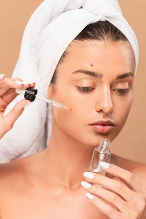 naked woman applying serum on face with pimples isolated on beige