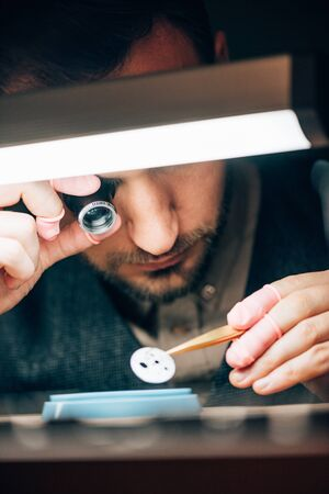 Selective focus of watchmaker holding eyeglass loupe and watch part at working table