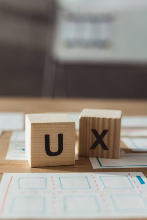 Selective focus of cubes with ux letters and layouts of user experience design on table