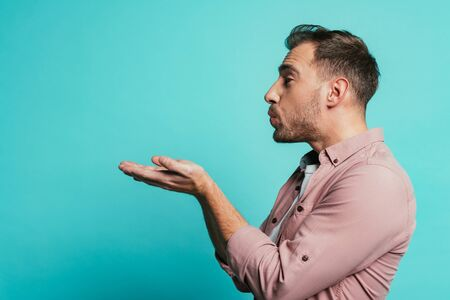 happy handsome man blowing air kiss isolated on blue